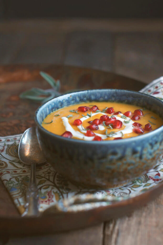 Side view of a bowl roasted acorn squash soup garnished with sage, pomegranate and sour cream