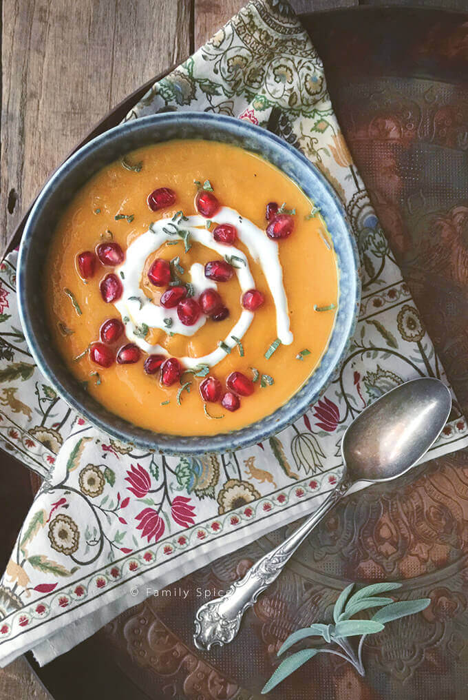 Overhead shot of a bowl of roasted acorn squash soup with sage and sour cream studded with pomegranate by FamilySpice.com