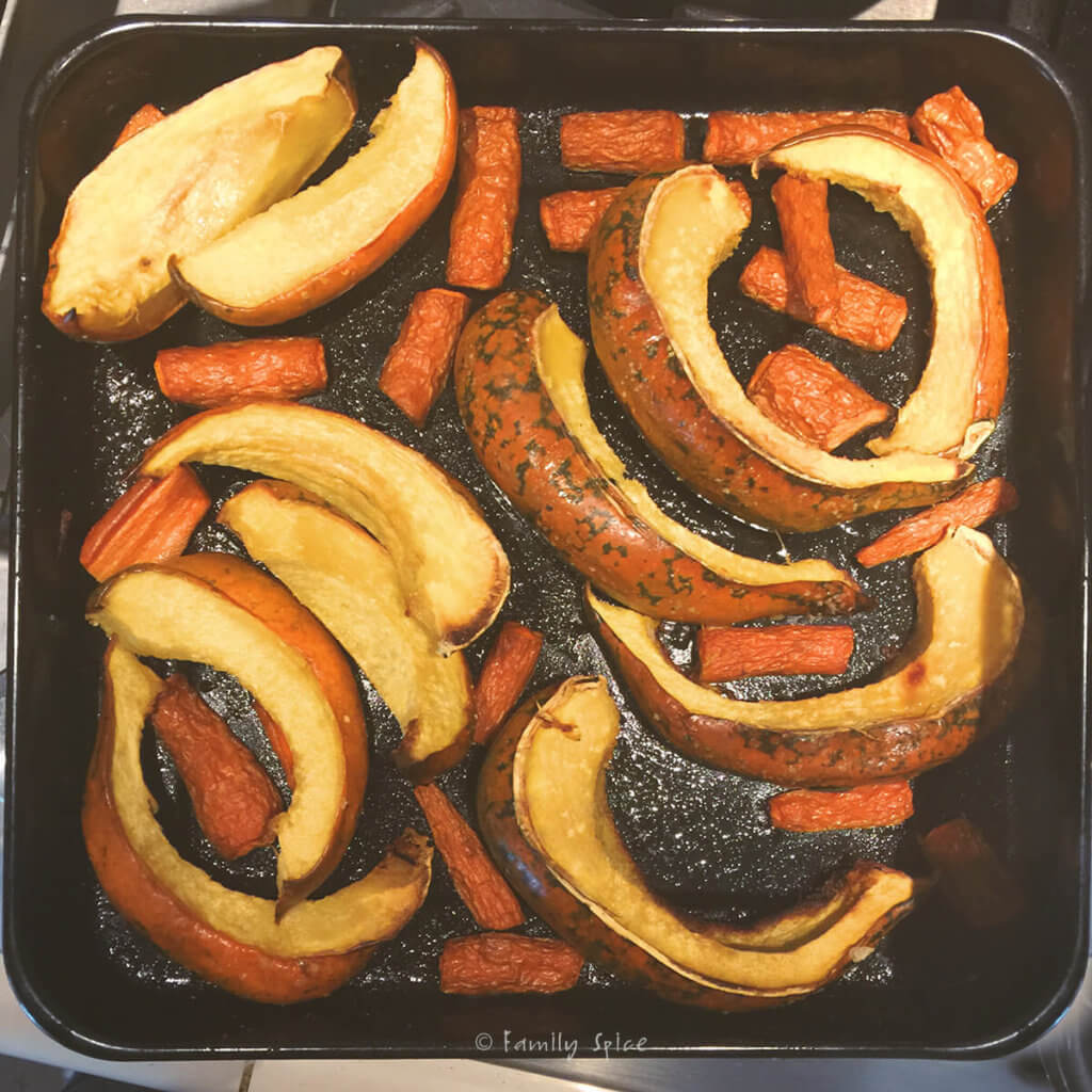 A baking sheet with roasted acorn squash slices and carrots