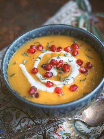 Closeup of a bowl of roasted acorn squash soup garnished with sage, pomegranate and sour cream