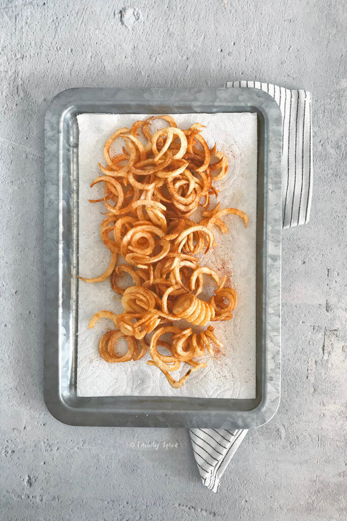 Seasoned curly fries sitting on a metal tray lined with paper towels