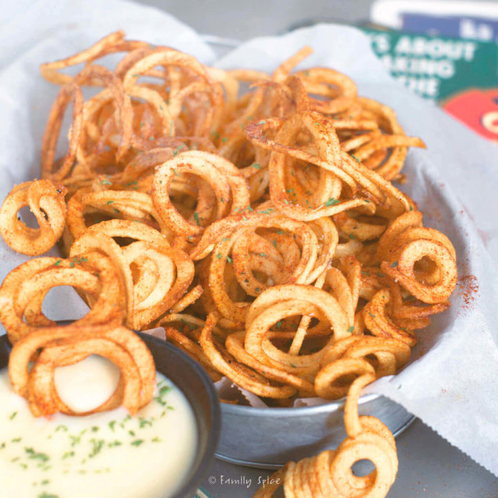Closeup of a metal basket filled with curly fries with a small bowl of beer cheese dip next to it
