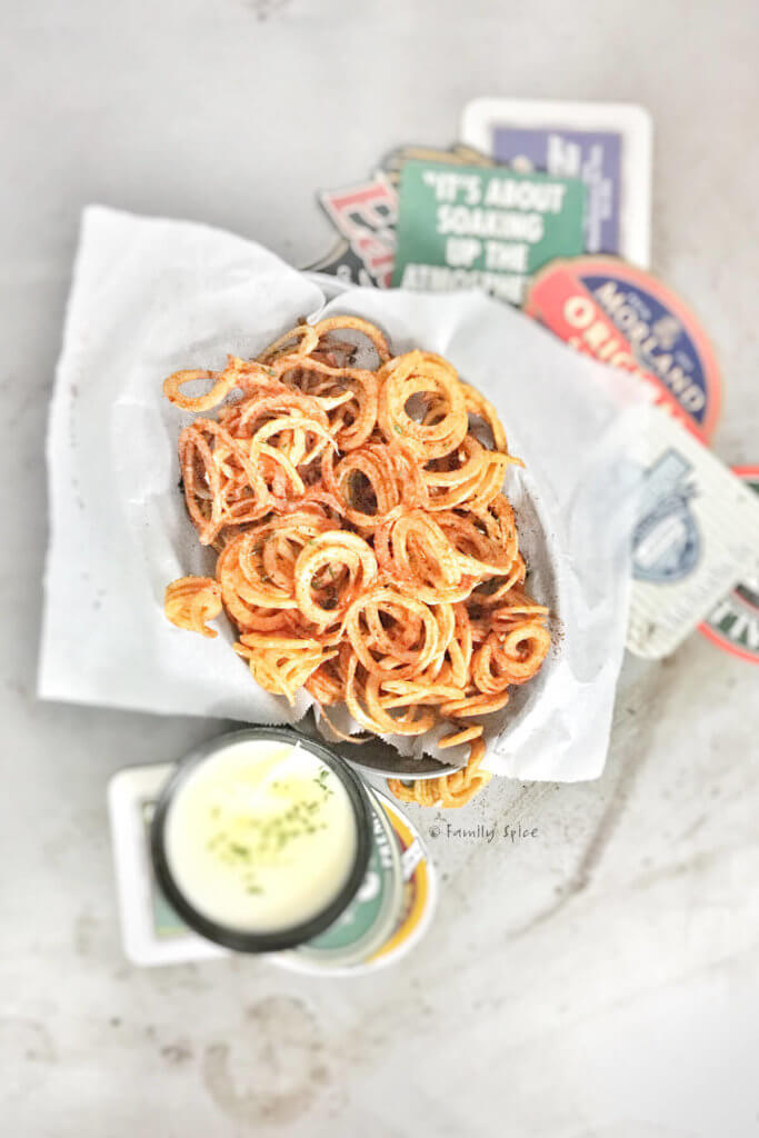 Overhead shot of a basket filled with curly fries with a small bowl of beer cheese dip next to it