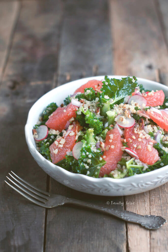 A white bowl with kale, grapefruit, quinoa salad on a rustic background