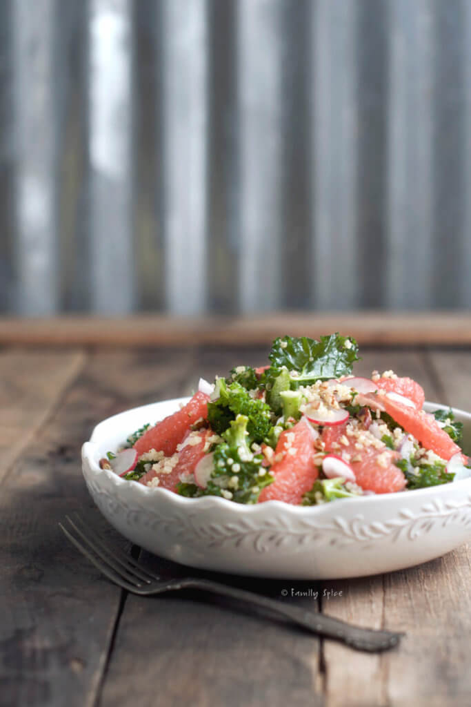 Side view of a white bowl with kale, grapefruit, quinoa salad on a rustic background