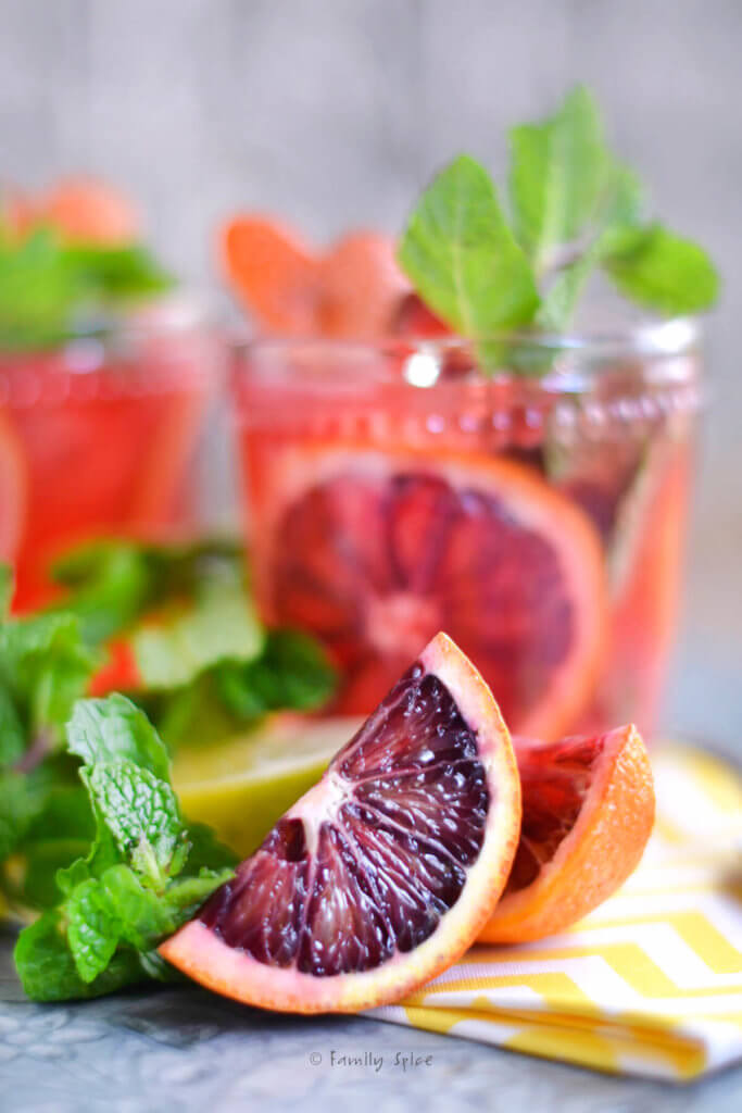Closeup of a wedge of blood orange with two glasses with blood orange mojito behind it