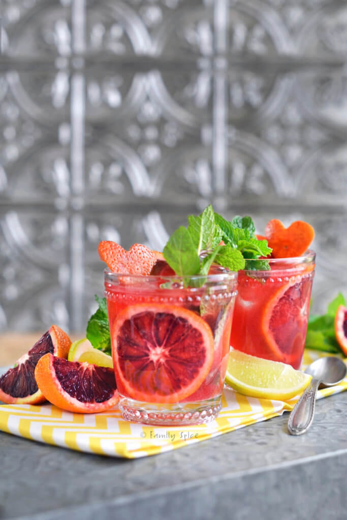Two glasses filled with blood orange mojito and garnished with blood oranges and mint