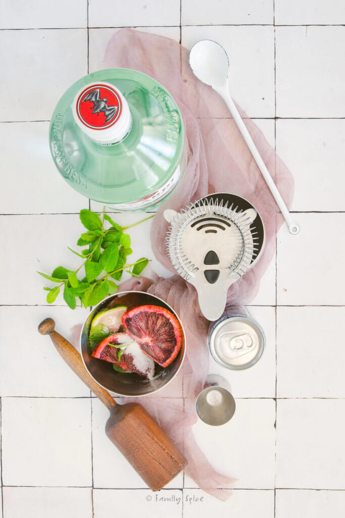 A cocktail shaker with ingredients to make blood orange mojito with a wooden muddler and other bar accessories next to it