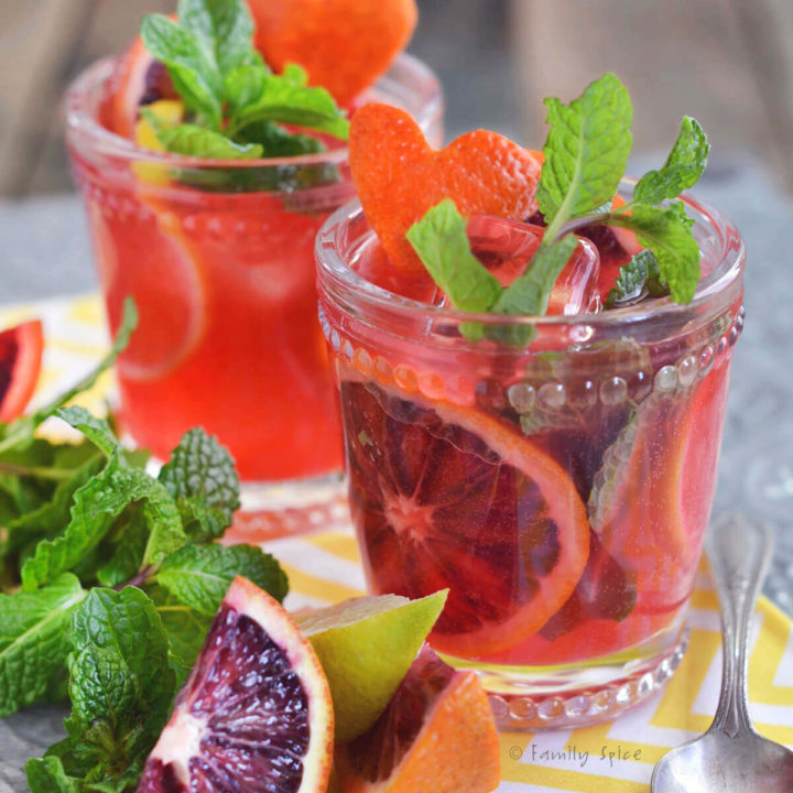 Close up of two glasses filled with blood orange mojito and garnished with blood oranges and mint