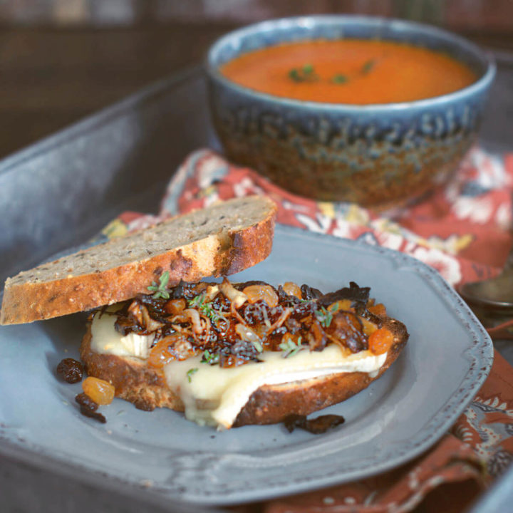 Toasted brie sandwich with caramelized onions and raisins on a gray plate with a bowl of tomato soup behind it