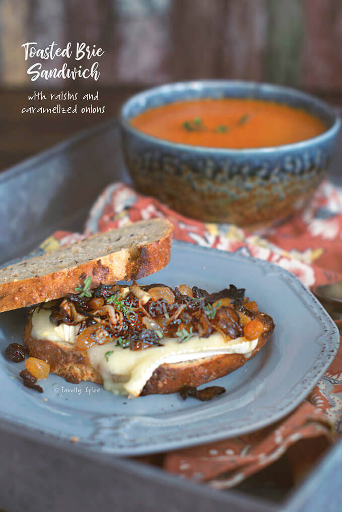 A tray holding a melted brie sandwich with onions and raisins and a bowl of tomato soup in the background by FamilySpice.com