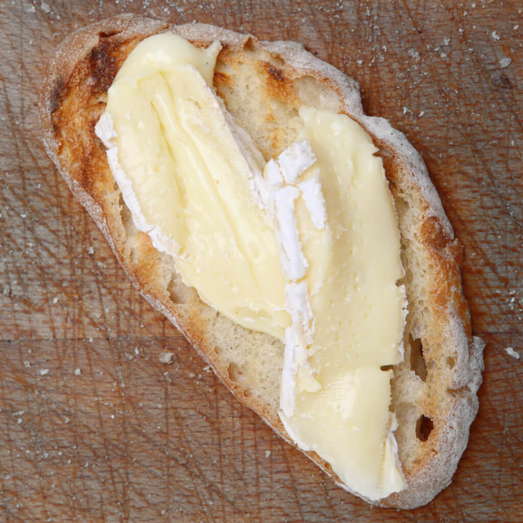 Slices of brie on a bread on a wood surface