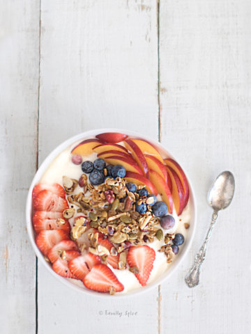 A bowl of yogurt with fruit and granola on a white background