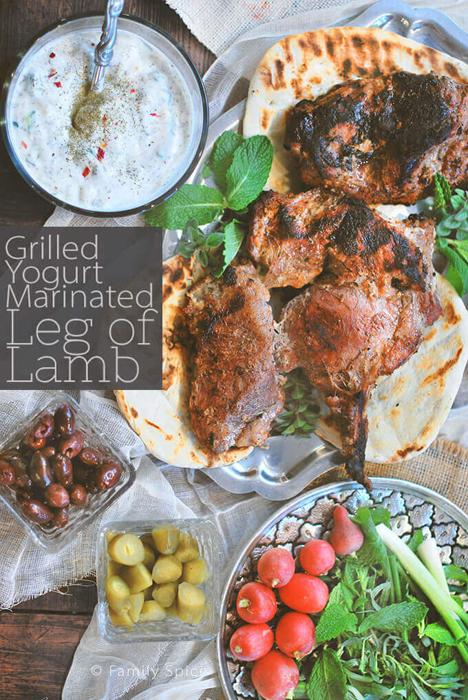 A platter of grilled butterflied leg of lamb marinated in yogurt served with yogurt, radishes, herbs, pickles and olive by FamilySpice.com