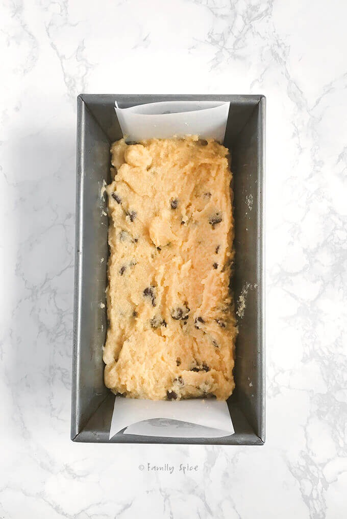 Paleo chocolate chip cookie bars batter in a loaf pan ready to bake by FamilySpice.com