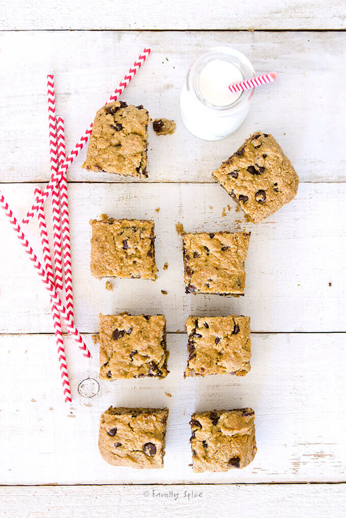 Overhead shot of 8 chocolate chip cookie bar with with a small milk bottle and several red and white straw by FamilySpice.com