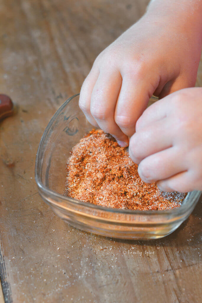 A child's hand mixing up seasonings