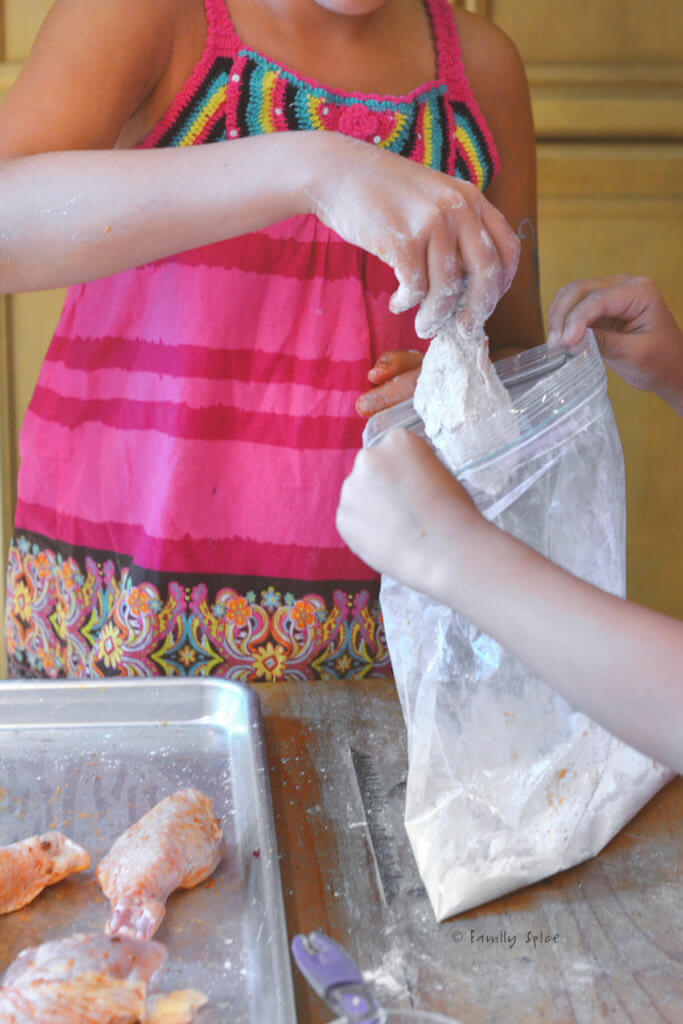 Kids putting seasoned chicken legs in a bag with flour to coat with flour