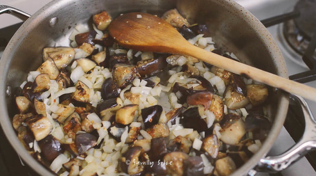 A stainless steel pan on the stove with eggplant and onions cooking