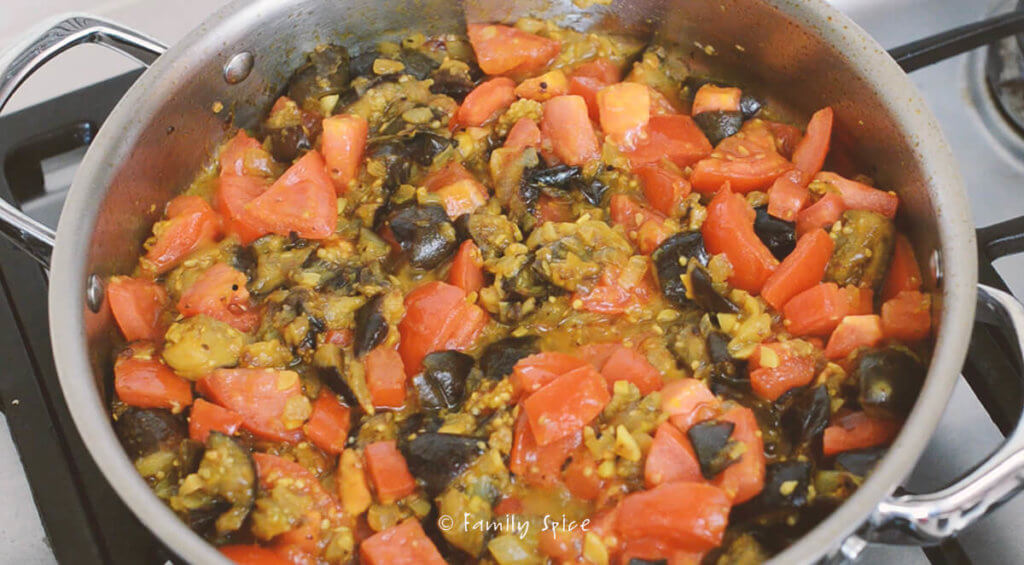 A stainless steel pan on the stove with eggplant, tomatoes and onions cooking with turmeric