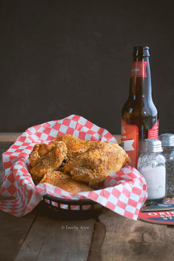 A paper lined basket with oven fried chicken pieces and a bottle of beer next to it