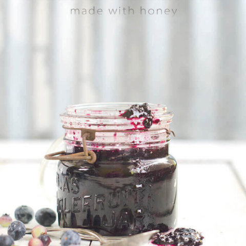 A jar of blueberry jam with blueberries around it