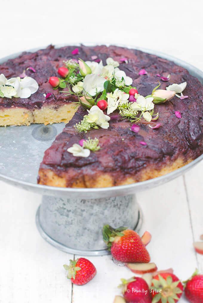 Closeup of strawberry rhubarb upside down cake on a metal cake stand by FamilySpice.com