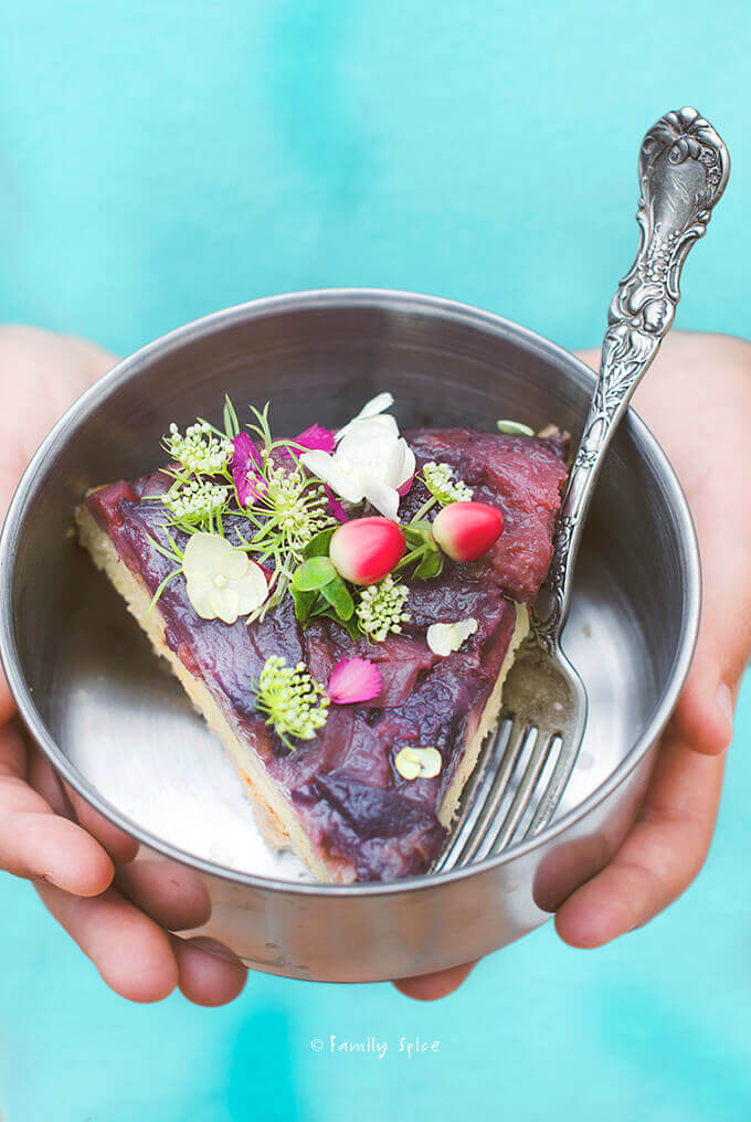 A slice of strawberry rhubarb upside down cake in a metal bowl and turquoise background by FamilySpice.com