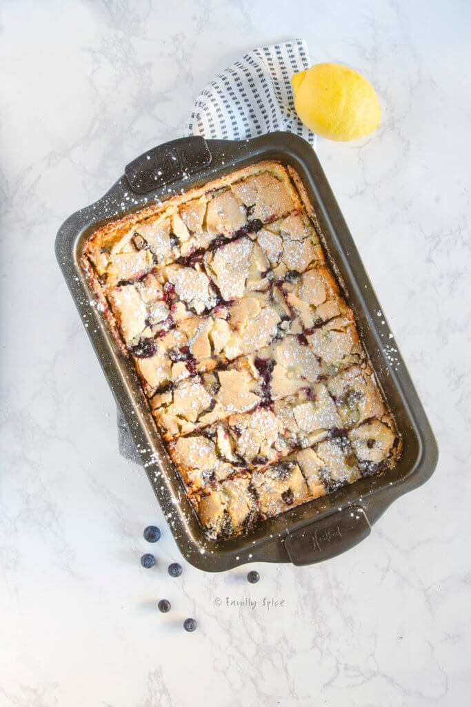 Powdered sugar dusted lemon bars cut into squares in a baking pan with a lemon next to it