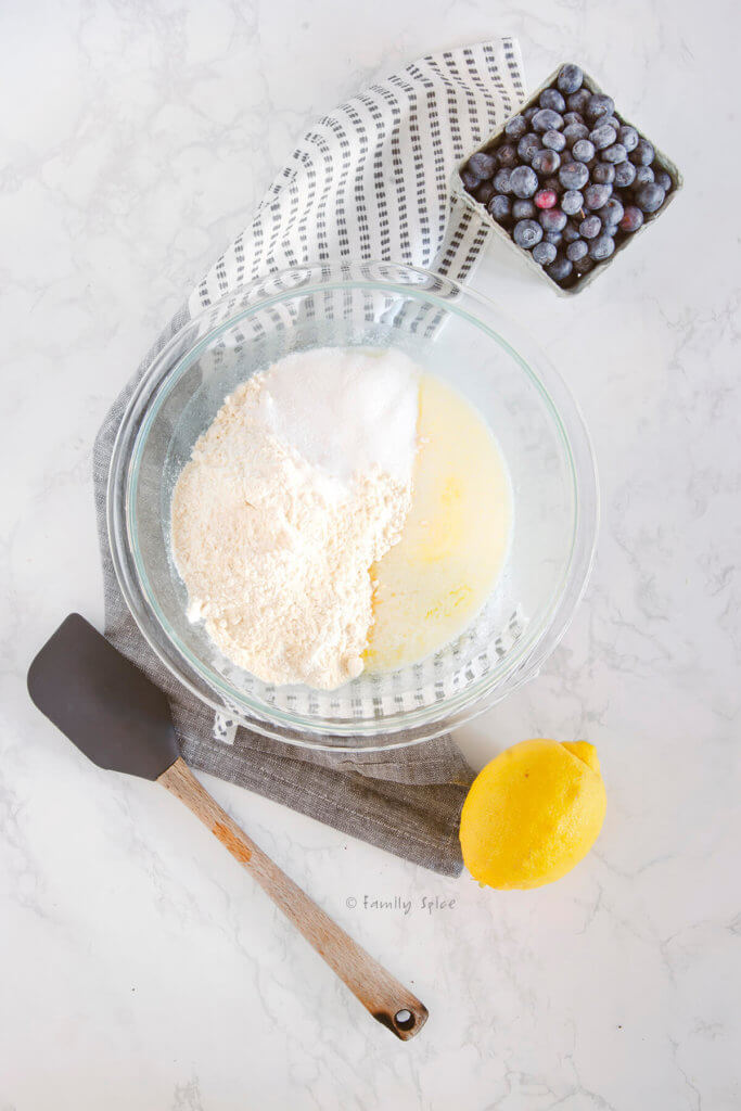 A mixing bowl with melted butter, sugar and flour in it with a lemon and blueberries next to it