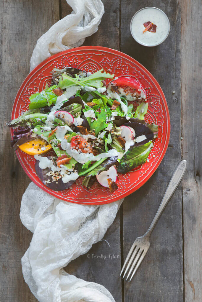 Overhead shot of a red plate with salad, tomatoes, quinoa and homemade ranch dressing