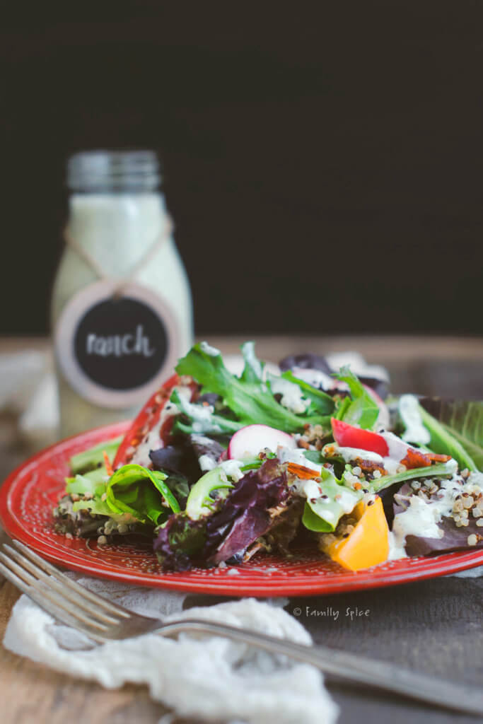 Side view of a red plate with salad, tomatoes, quinoa and homemade ranch dressing with a bottle of dressing in the background