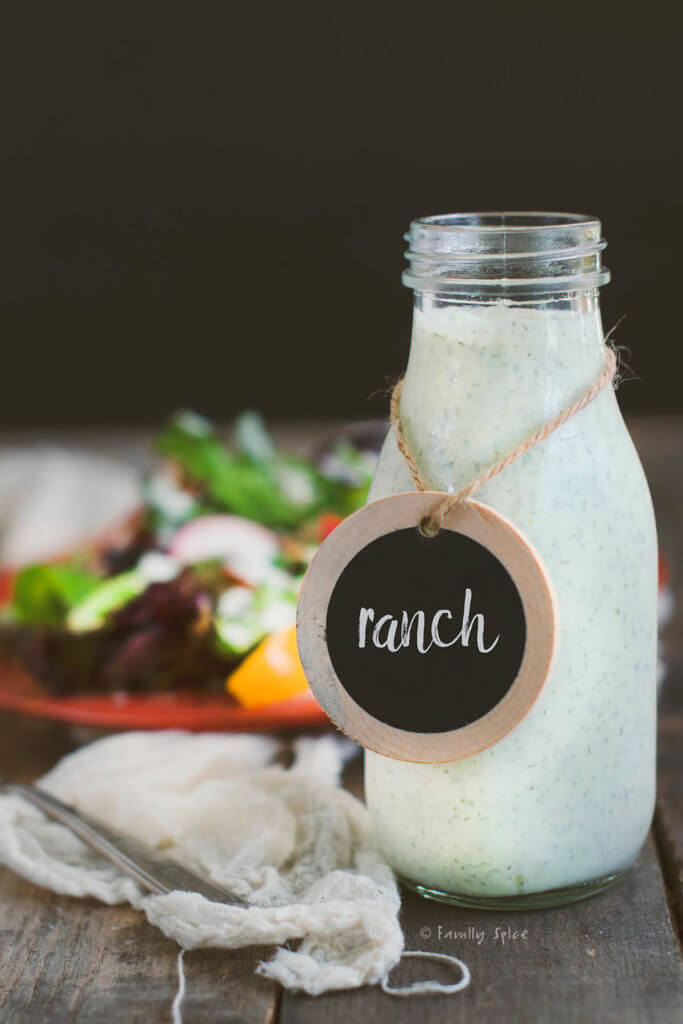 A bottle of homemade ranch dressing Side with a red plate with salad in the background