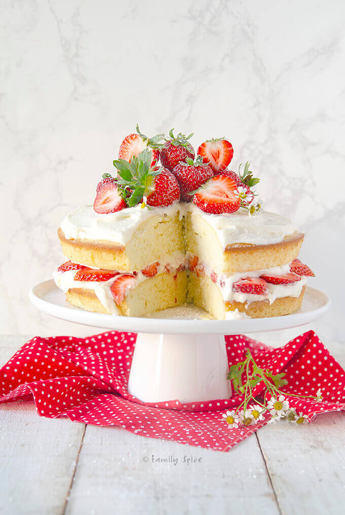 Easy olive oil vanilla cake cut open and frosted and stuffed with fresh strawberries by FamilySpice.com