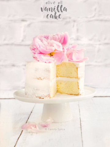 Easy olive oil vanilla cake cut open and frosted in white and topped with a pink flower by FamilySpice.com