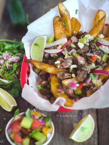 Closeup of a basket with loaded carne asada fries with ingredients around it
