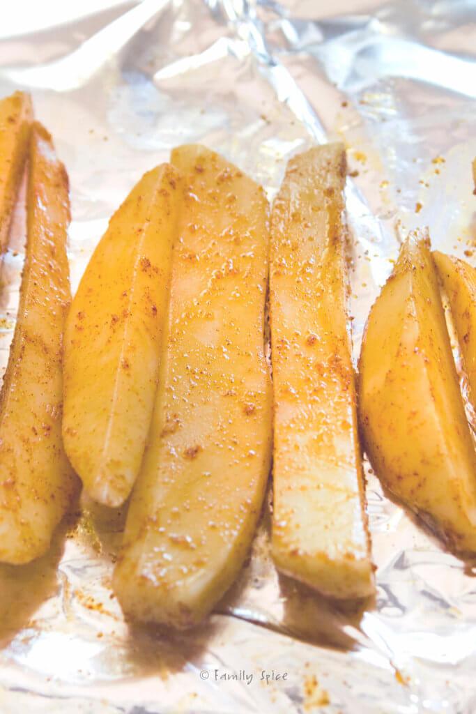 Seasoned potato wedges on foil