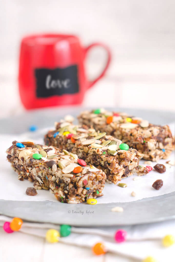 Three crispy rice bars on a silver platter with a red mug behind it
