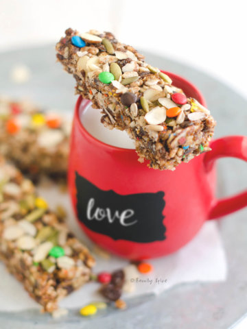 A crispy rice bar sitting on top of a red mug filled with milk on a platter with more bars