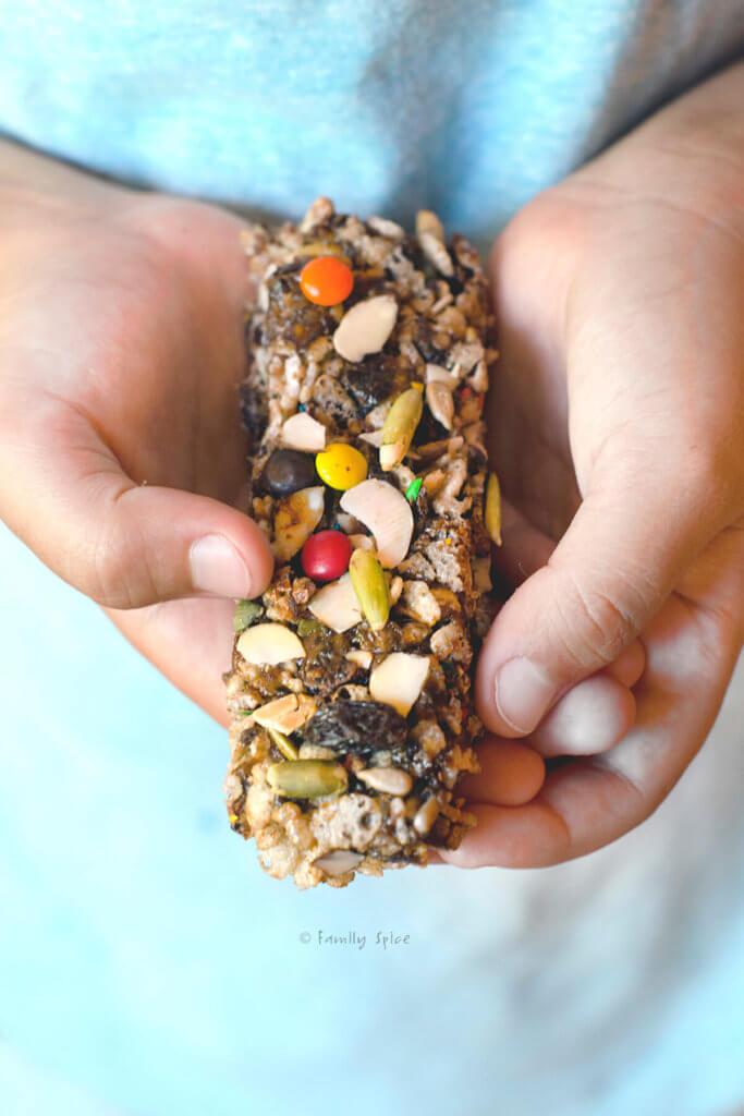 A child's hand holding a crispy rice bar