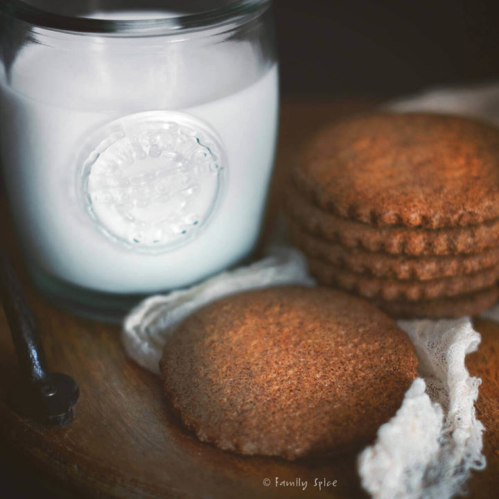 Closeup of quinoa spice cookies on a wood tray with a glass of milk