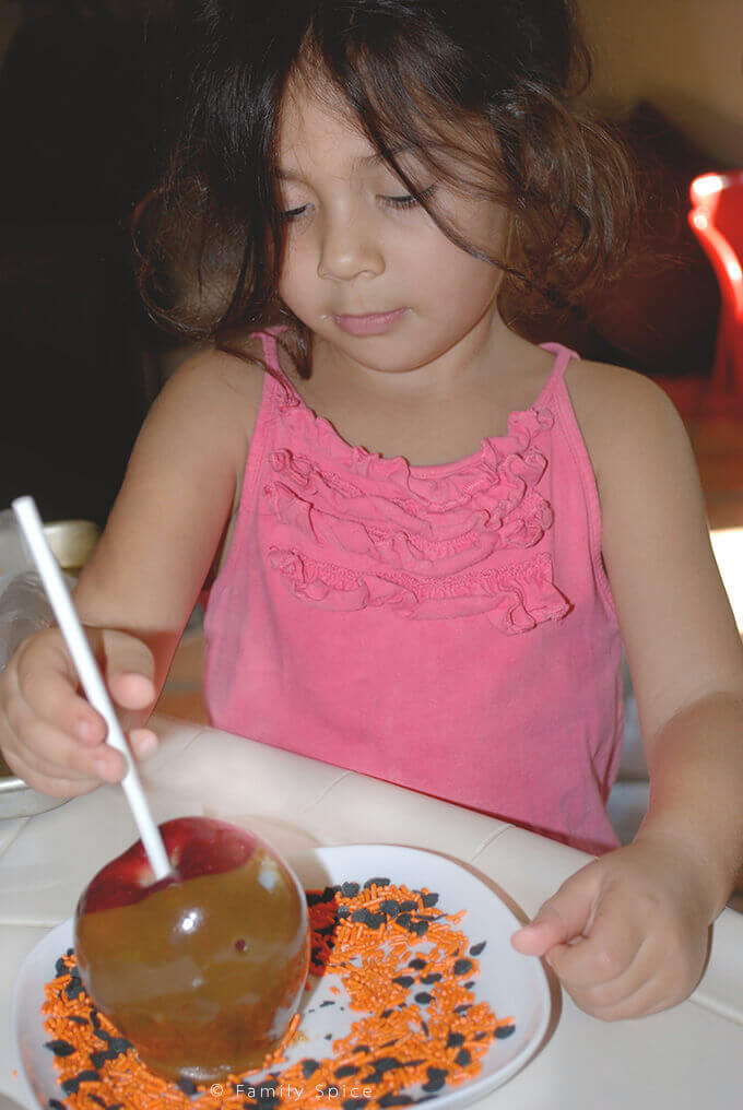 My girl dipping caramel apples in sprinkles by FamilySpice.com