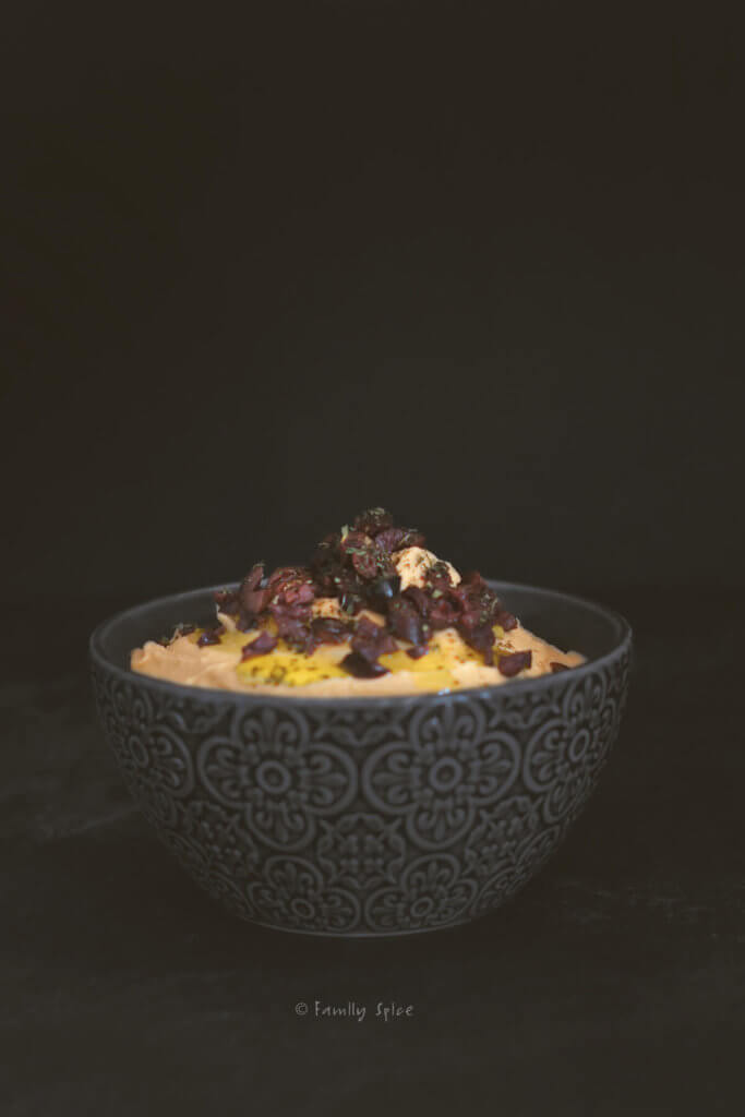 Side view of a dark charcoal bowl with pumpkin hummus in it and garnished with olives and olive oil