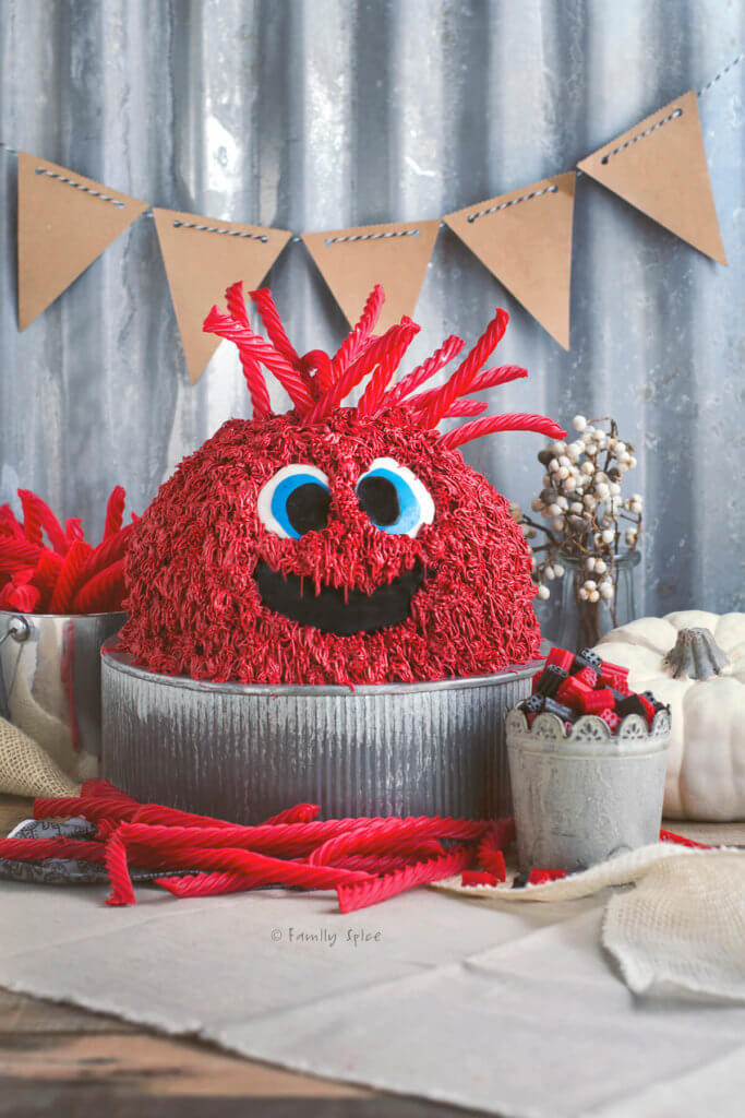 A red monster cake with red vine candy hair with more candies around it