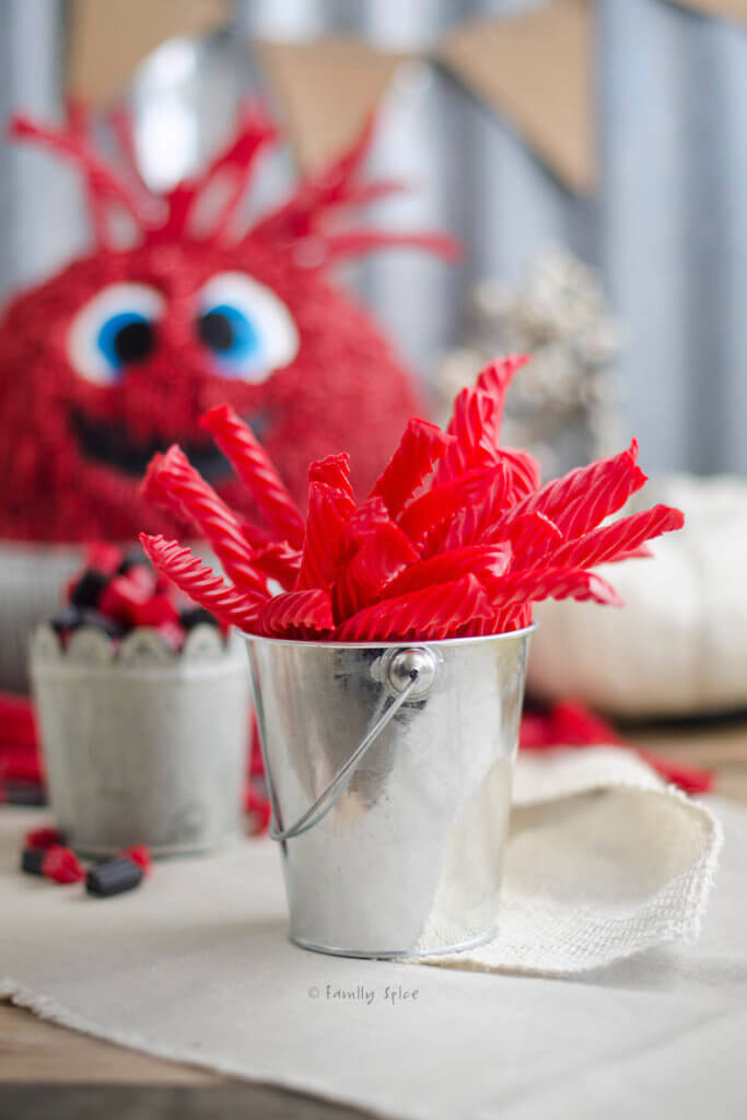 A metal cup with red red vine candies in it and monster cake behind it