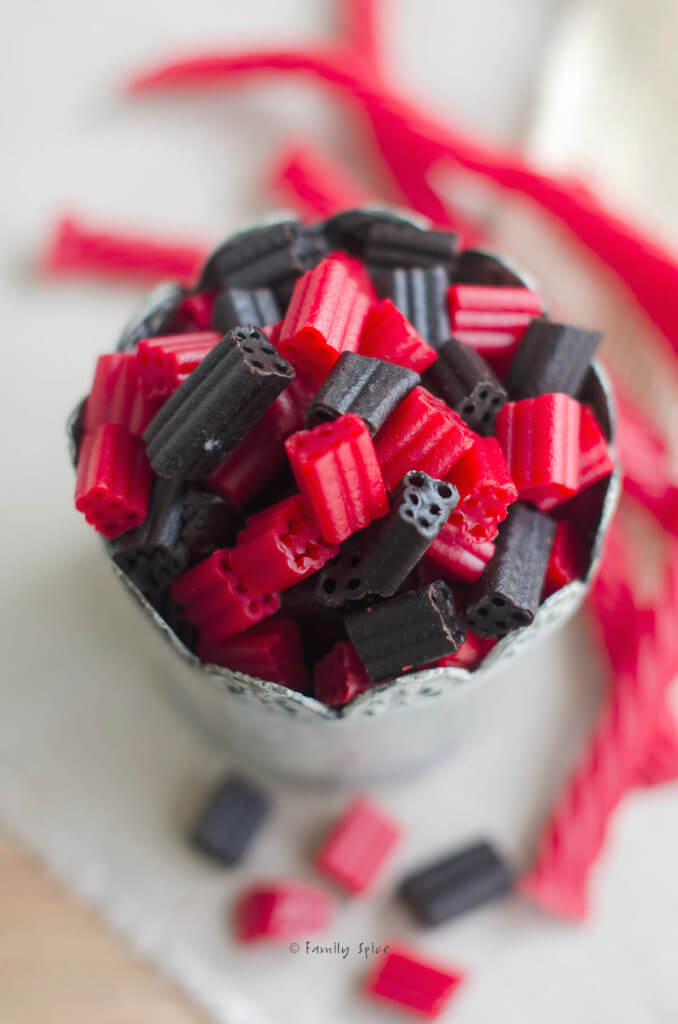 Close up of a metal cup with red and black candies in it