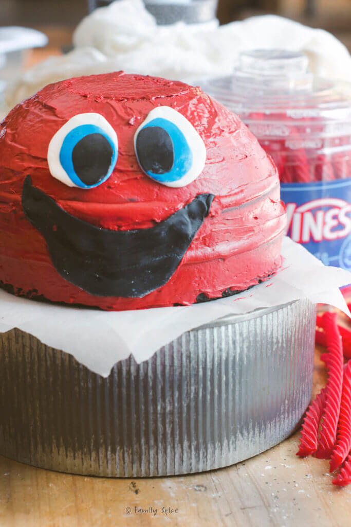 A red monster cake with fondant eyes and mouth attached