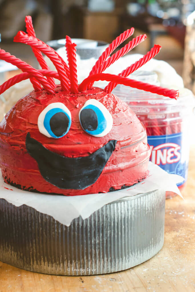 Making a red monster cake with fondant eyes and mouth plus red vine hair attached