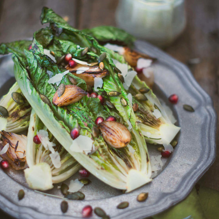 Closeup of a pewter plate with grilled romaine lettuce topped with roasted shallots and pomegranate arils