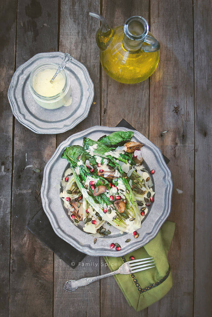 Overhead shot of a dish with Grilled Caesar Salad with pomegranate, pepitas and shallots by FamilySpice.com